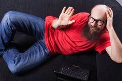 Mężczyzna na kanapie jest szczęśliwy i falowanie - (serie) Zdjęcia Stock