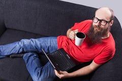 Mężczyzna na kanapie odpoczywa i pije, - (serie) Zdjęcia Stock