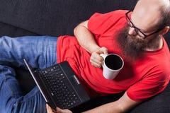 Mężczyzna na kanapie ogląda film i pije, - (serie) Zdjęcia Stock