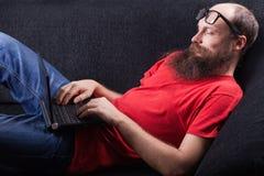 Mężczyzna na kanapie pracuje - (serie) Obrazy Stock