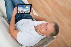 Mężczyzna Na kanapie Z laptopem Pokazuje ikony Zdjęcie Stock