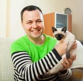 Mężczyzna na leżance z małym zwierzęciem domowym fotografia stock
