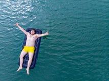 Mężczyzna na materac w błękitne wody Lato czasu pojęcie Zdjęcia Stock