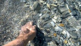 Mężczyzna na oceanów chwytach w jego ręka otoczak