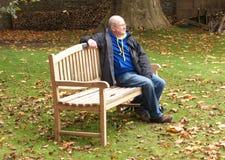 Mężczyzna na parkowej ławce w jesieni fotografia royalty free