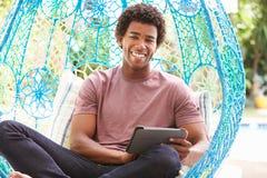 Mężczyzna Na Plenerowej ogród huśtawce Seat Używać Cyfrowej pastylkę obrazy royalty free