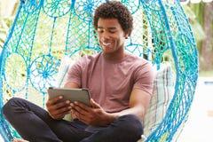 Mężczyzna Na Plenerowej ogród huśtawce Seat Używać Cyfrowej pastylkę zdjęcie stock