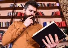 Mężczyzna na ruchliwie rozważnej twarzy czytelniczej książce, półka na książki na tle Edukaci i nauki pojęcie Nauczyciel lub ucze Zdjęcie Stock