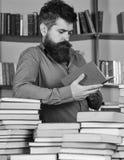 Mężczyzna na ruchliwie rozważnej twarzy czytelniczej książce, półka na książki na tle Edukaci i nauki pojęcie Nauczyciel lub ucze Obrazy Royalty Free