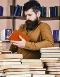 Mężczyzna na ruchliwie rozważnej twarzy czytelniczej książce, półka na książki na tle Edukaci i nauki pojęcie Nauczyciel lub ucze Zdjęcie Royalty Free