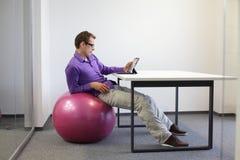 mężczyzna na stabilności piłce przy biurkiem Fotografia Royalty Free