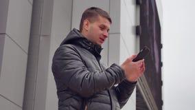 Mężczyzna na twój smartphone pisać na maszynie wiadomości tekstowej i patrzeć parawanową zimę w kurtce outdoors zdjęcie wideo