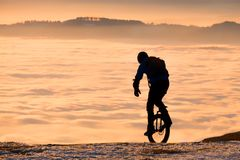 Mężczyzna na unicycle jazdie na górze nad mgłą zmierzch Fotografia Royalty Free