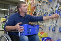 Mężczyzna na wózka inwalidzkiego kupienia narzędziach przy sklepem Fotografia Royalty Free