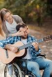 Mężczyzna na wózku inwalidzkim bawić się gitarę w parku Kobieta przychodził on od behind i zamkniętego ona oczy z jej rękami zdjęcie stock