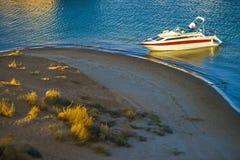 MĘŻCZYZNA NA władzy łodzi PRZY WODNĄ krawędzią plażą W OPÓŹNIONYM zmierzchu Zdjęcia Royalty Free