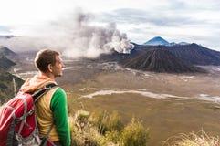 Mężczyzna na wzgórzu jest przyglądający na Bromo wulkanu erupci Bromo Tengger Semeru park narodowy Obrazy Stock