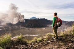 Mężczyzna na wzgórzu jest przyglądający na Bromo wulkanu erupci Bromo Tengger Semeru park narodowy Obraz Stock