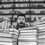 Mężczyzna na zdziwionej twarzy między stosami książki, podczas gdy studiujący w bibliotece, półka na książki na tle Nauczyciel lu obraz royalty free
