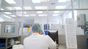 Mężczyzna naciera obiektyw w lab plecy widoku zbiory