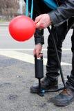 m??czyzna nadyma czerwonego balon z pomp? obraz stock