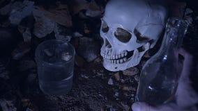 Mężczyzna nalewa alkohol i pije na tle czaszka alkoholu nałogu cincept 4K zdjęcie wideo