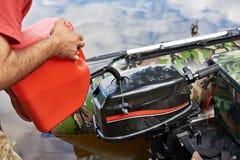 Mężczyzna nalewa benzynę w silnika łódź rybacka Obraz Stock