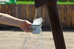 Mężczyzna nalewa filiżankę woda od szpaltowego (żuraw) Obraz Stock