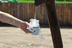Mężczyzna nalewa filiżankę woda od szpaltowego (żuraw) Fotografia Stock