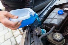 Mężczyzna nalewa płynu niezamarzającego fluid w jego samochód fotografia royalty free