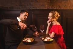 Mężczyzna nalewa wino w szkło, para w restauraci Zdjęcie Royalty Free