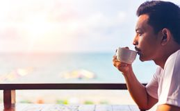 Mężczyzna napoju kawa blisko plaży stoi na plaży i jest ubranym białą koszula fotografia stock