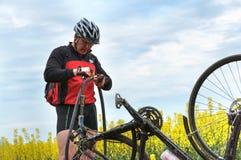 Mężczyzna naprawia bicykl w polu, dziurawienie Rowerowa kamera na sposobie zdjęcia royalty free