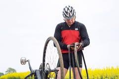 Mężczyzna naprawia bicykl w polu, dziurawienie Rowerowa kamera na sposobie zdjęcie royalty free