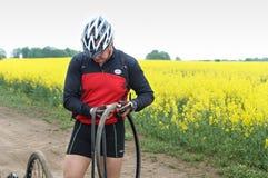 Mężczyzna naprawia bicykl w polu, dziurawienie Rowerowa kamera na sposobie zdjęcie stock