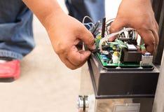 Mężczyzna naprawia elektronicznego system kontrolnego Obrazy Stock