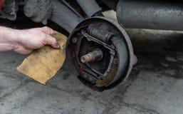 Mężczyzna naprawia hamulcowych bębeny dla samochodu i czyści hamulcowych ochraniaczów z szklakiem fotografia stock