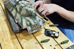 Mężczyzna naprawia obniżonego modela sowiecki zbiornik T-34 Obrazy Royalty Free