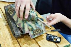 Mężczyzna naprawia obniżonego modela sowiecki zbiornik T-34 Zdjęcie Stock