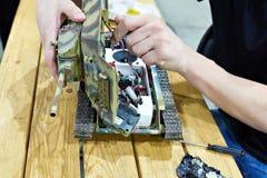 Mężczyzna naprawia obniżonego modela sowiecki zbiornik T-34 Fotografia Stock