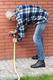 Mężczyzna naprawia przeciekającego ogrodowego węża elastycznego czopek Obraz Stock