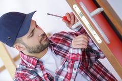 Mężczyzna naprawiania kędziorek w starym drzwi fotografia stock