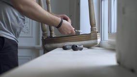 Mężczyzna naprawiania krzesło w pokoju zbiory
