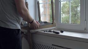 Mężczyzna naprawiania krzesło w pokoju zbiory wideo