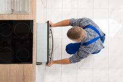 Mężczyzna naprawiania kuchni piekarnik obraz royalty free