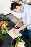 Mężczyzna narządzania kucharstwo w kuchni i sałatka Obraz Stock