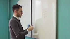Mężczyzna nauczyciel pisze na białej desce w klasowym pokoju zbiory