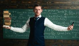 Mężczyzna nauczyciela równoważenie w ręka stosie książki i smartphone jako symboli/lów ewidencyjni storages analogowi i cyfrowi n Fotografia Stock
