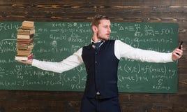 Mężczyzna nauczyciela równoważenie w ręka stosie książki i smartphone jako symboli/lów ewidencyjni storages analogowi i cyfrowi n Zdjęcia Royalty Free