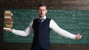 Mężczyzna nauczyciela równoważenie w ręka stosie książki i smartphone jako symboli/lów ewidencyjni storages analogowi i cyfrowi R Zdjęcie Stock